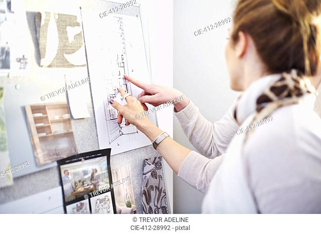 Interior designers discussing blueprints hanging in office