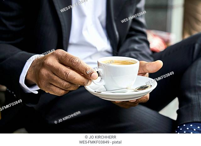 Man sitting in cafe, drinking coffee