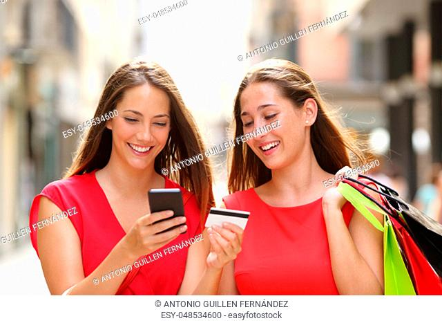 Front view of two happy shoppers buying online with credit card and cellphone walking in the street
