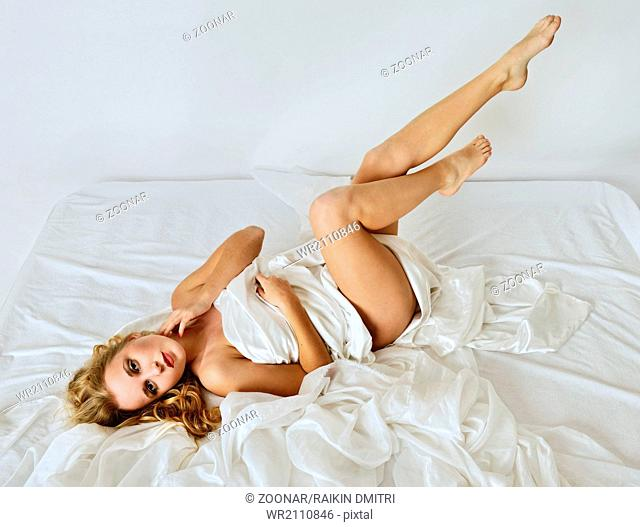 Beautiful naked woman on white bed