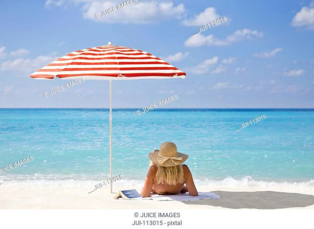 Woman relaxing on sunny beach with book under striped beach umbrella