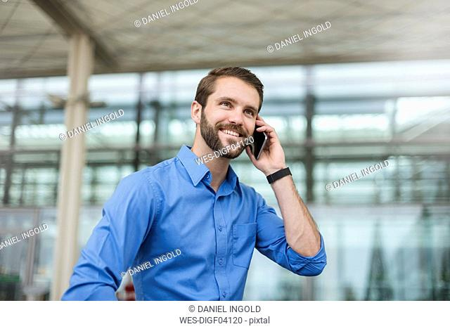 Smiling young businessman on cell phone outdoors