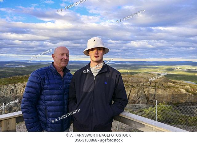 Father and son admire the city views of the iron mining town of Kiruna. Kiruna, Sweden