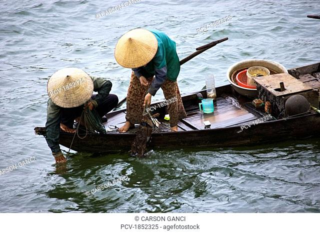 Women fishing on a small boat in Vietnam