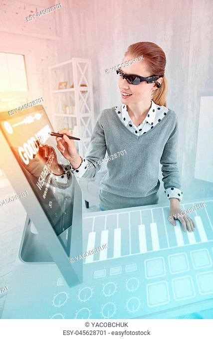 Creative person. Clever experienced web designer smiling while wearing virtual reality glasses and holding a convenient stylus