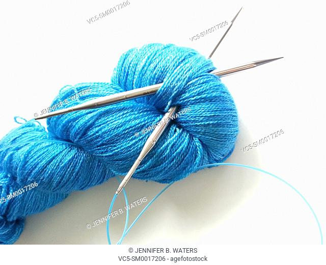 Close-up of yarn and knitting needles on a white background