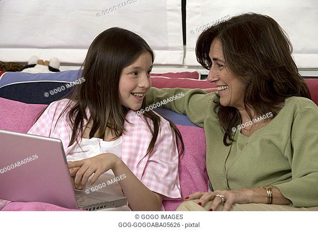 Mother and daughter using a laptop in bedroom
