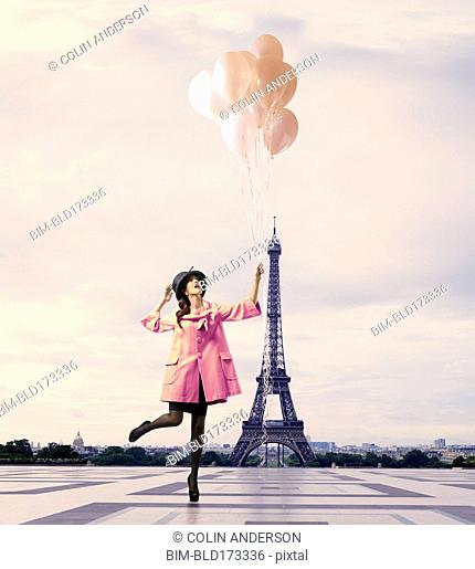 Pacific Islander woman with balloons near Eiffel Tower, Paris, Ile