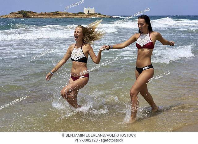 two women running at beach in sea water, wearing bikini. Having fun. Holiday location Greece, Crete, Malia