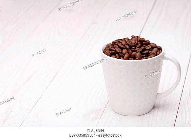 beautiful white coffee cup with coffee beans on wooden background