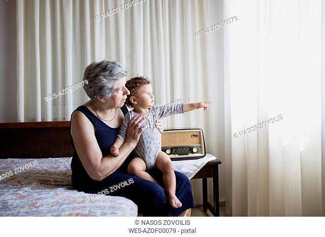Grandmother sitting on bed with her grandson
