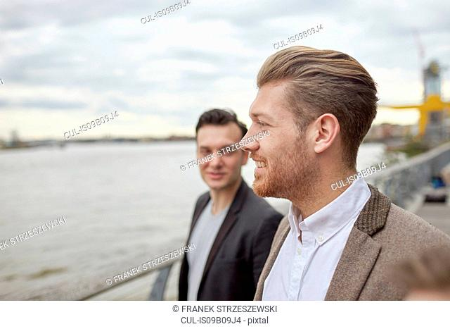 Two businessmen having discussion on waterfront, London, UK