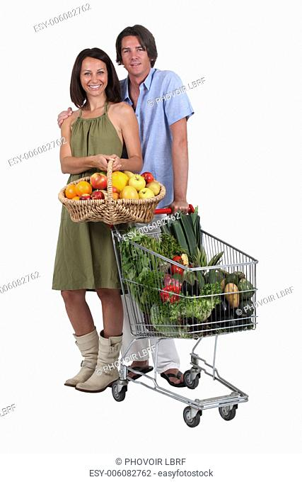 Couple with a basket and trolley full of fresh produce
