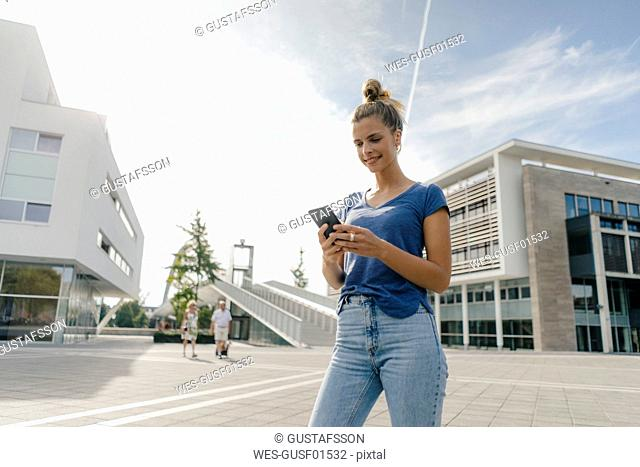 Netherlands, Maastricht, smiling young woman using cell phone in the city