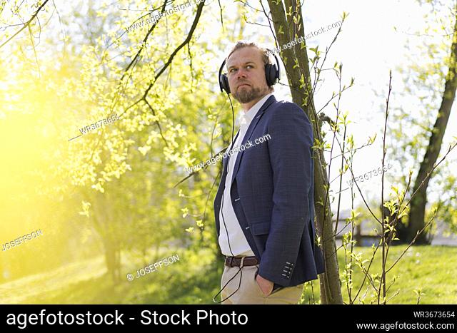 Male entrepreneur listening music while looking away at park on sunny day
