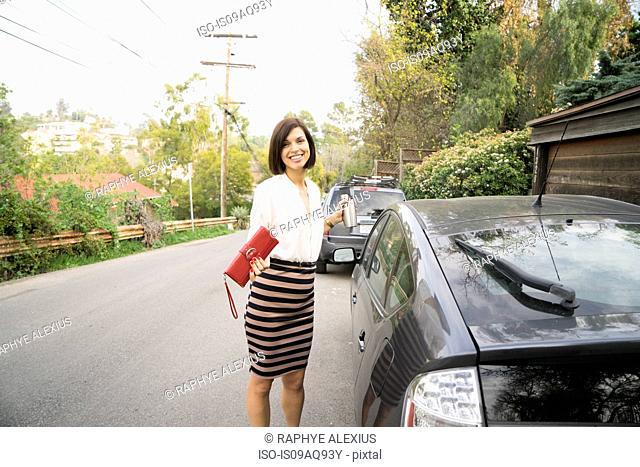 Portrait of businesswoman next to car on suburban street