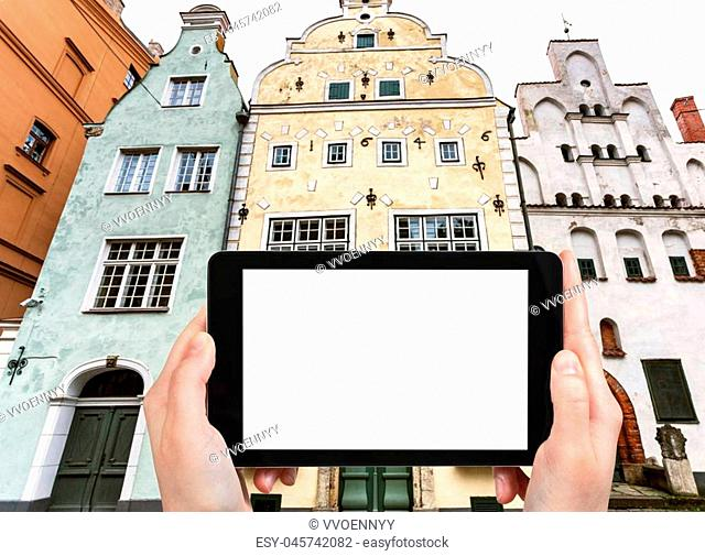 travel concept - tourist photographs Three Brothers, early Renaissance style houses, on Maza Pils iela in Old Riga Town Latvia in autumn on tablet with cut out...