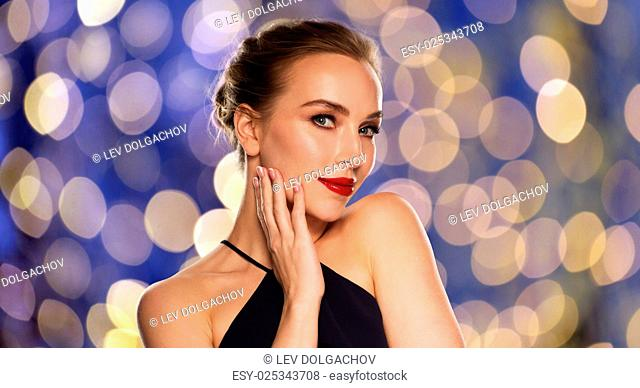 people, luxury and fashion concept - beautiful woman in black with red lips over blue holidays lights background