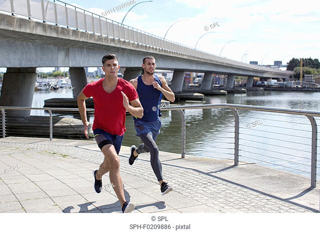Two men running by river
