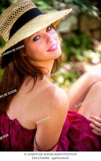 A pretty 25 year old brunette woman wearing a summer dress and a straw hat sitting in a garden, looking at the camera