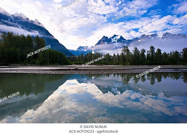 Coast mountains reflected in the Taku river, British Columbia, Canada