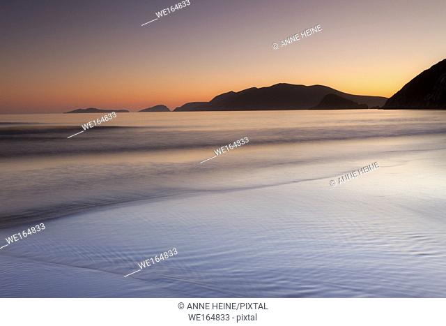tranquil beach after sunset with islands, dingle, ireland