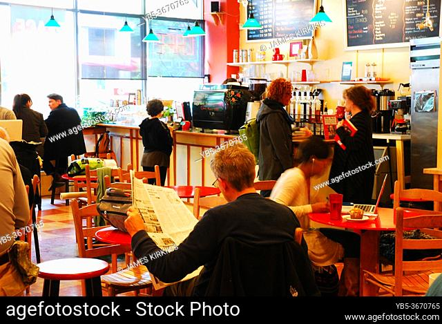 Folks chat with their friends and read the newspaper at a café and bookstore in Asheville, North Carolina