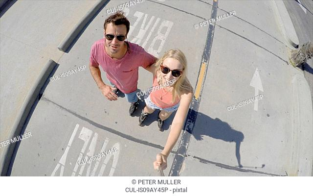 Couple rollerblading on cycle path taking selfie, Venice Beach, California, USA