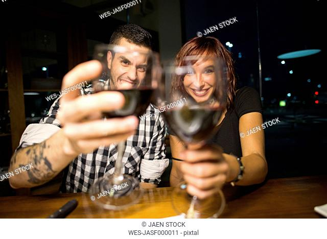 Happy young couple in a restaurant toasting with red wine glasses to the viewer