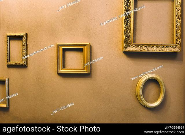 Empty golden luxury frames on vintage design wall, space for text. antique luxe interior background