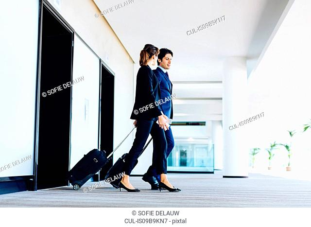 Businessman and businesswoman with wheeled luggage exiting hotel escalators