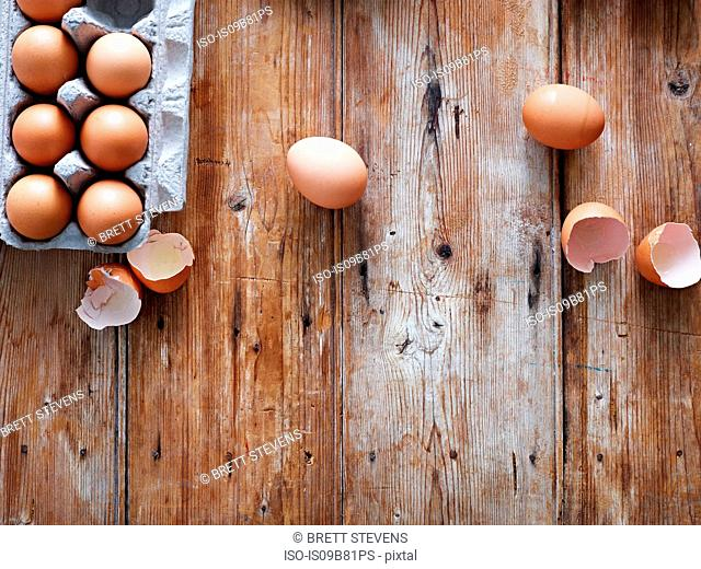 Eggs in egg box and broken shells on wooden surface, overhead view
