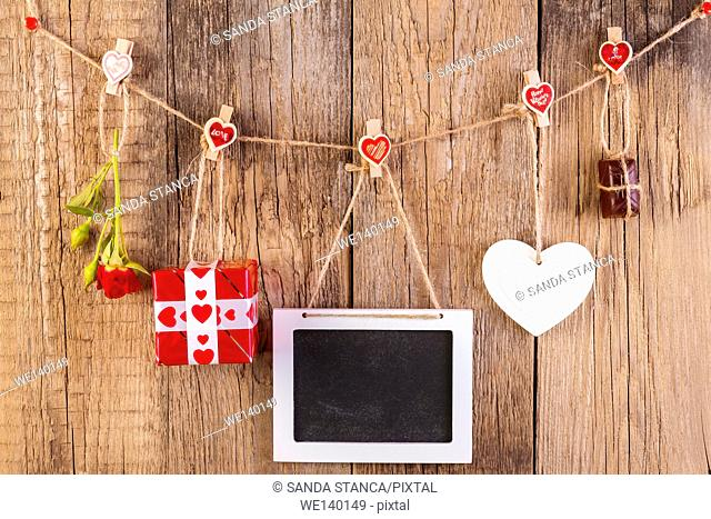 Red rose with gift box and white frame and chocolate on wooden background