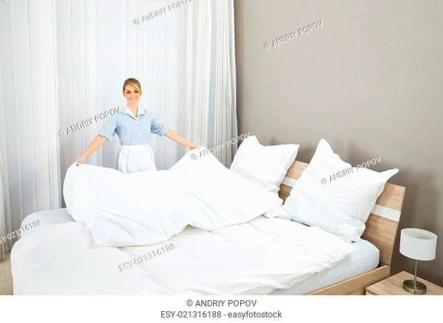 Happy Female Chambermaid Making Bed In Hotel Room