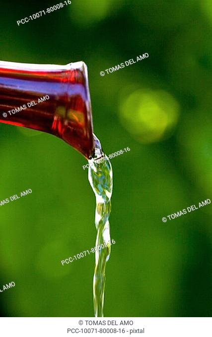 Spa elements, red glass spout pouring water, gren blurred background