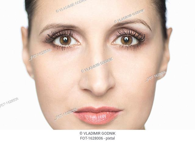 Close-up portrait of confident mid adult woman against white background