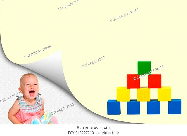Laughing toddler girl is sitting in an exposed corner of blank paper with colorful pyramid of wooden toy cubes