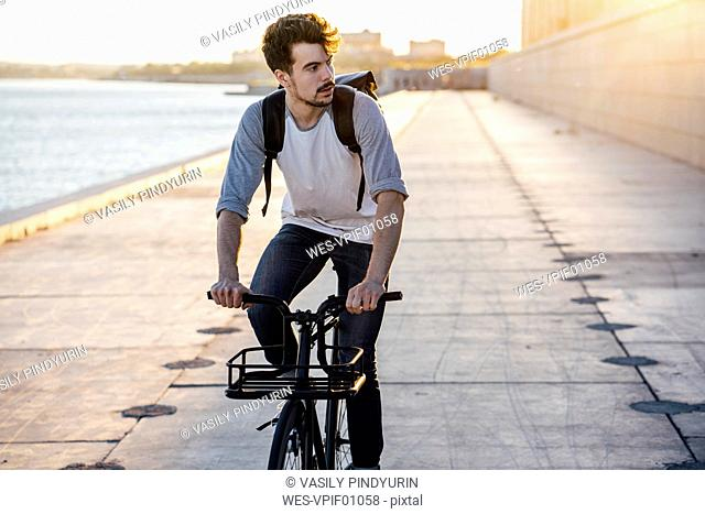 Young man with backpack riding bike on waterfront promenade at the riverside