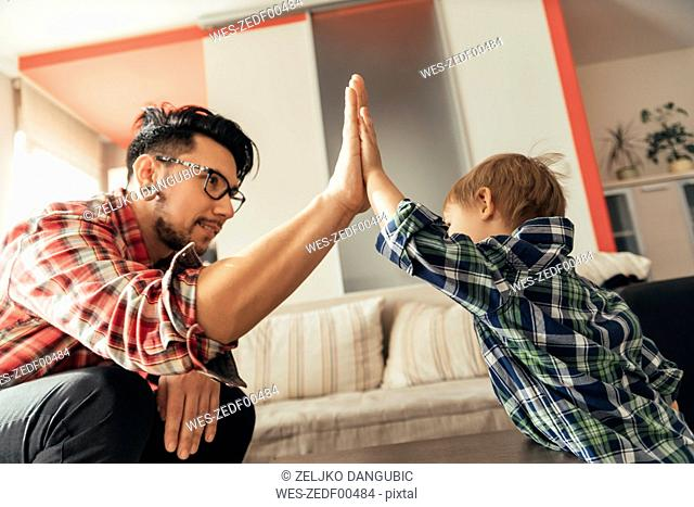 Father and son high fiving