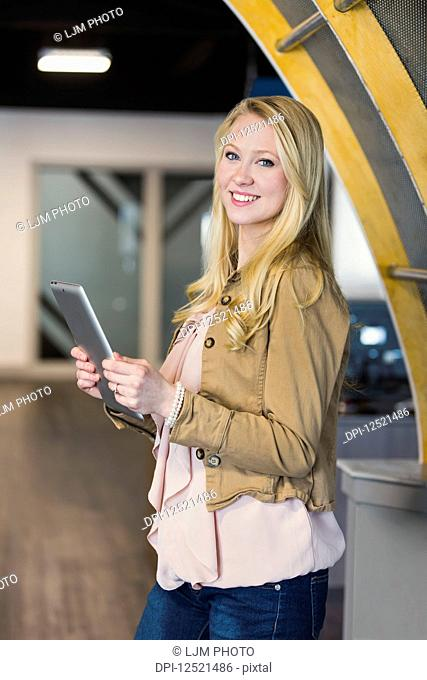 Business portrait of a beautiful young millennial professional using technology in the workplace; Sherwood Park, Alberta, Canada