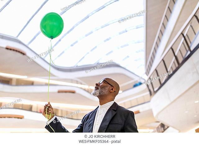 Mature businessman with green balloon