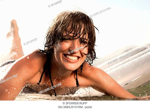 Woman floating on raft in water