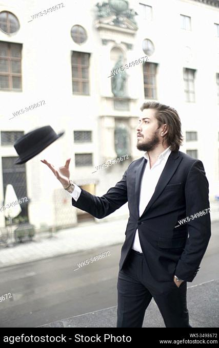 stylish man throwing hat in air