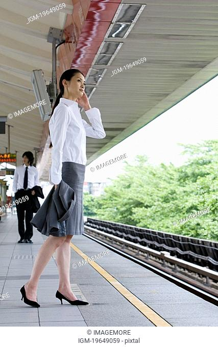 Businesswoman standing on train platform, using cell phone, businessman in the background