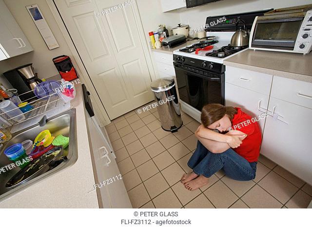 Woman sitting on floor in kitchen