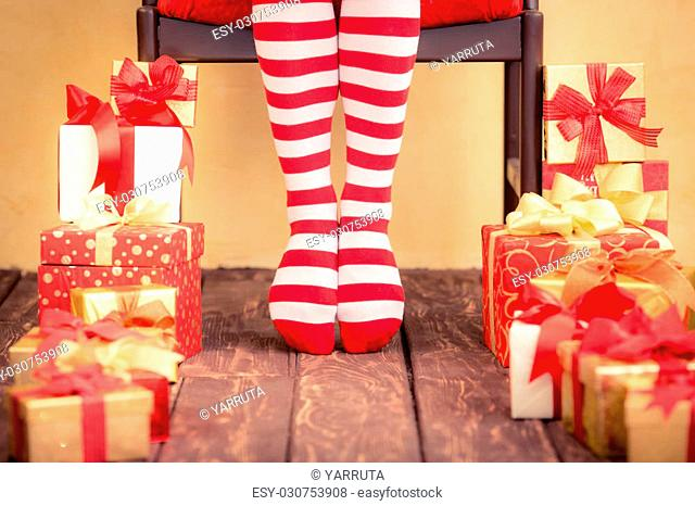 Sexy Santa woman legs and gift boxes. Christmas holiday concept