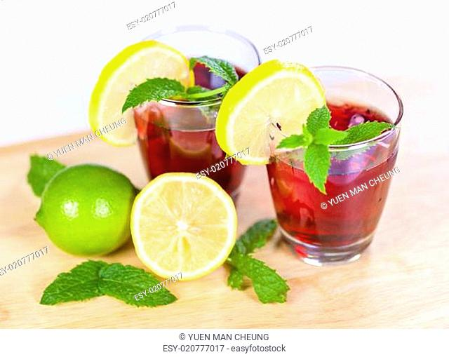 Two glasses of red fruit juice with lemon and lime