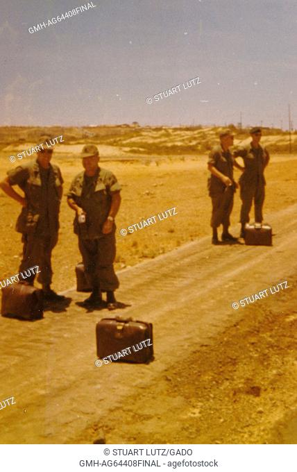 A group of four soldiers engage in conversation while they wait, with their suitcases, for their transport to arrive, rocky