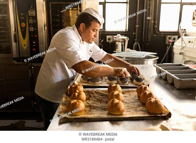Male baker preparing round croissants