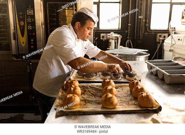 Male baker preparing round croissants